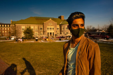 A student wearing a mask in front of Farinon College Center on the Quad.