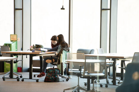 Masked students sit at tables in front of large windows at Rockwell Integrated Sciences Center