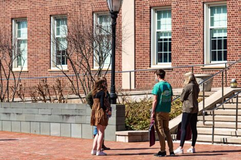 Three masked students talk to each other in a small group outside of Acopian Engineering Building.