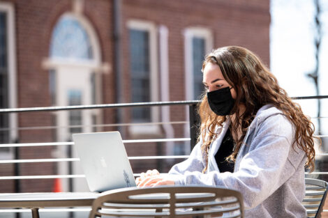 A masked student sits outside of Rockwell Integrated Sciences Center, with their laptop open.