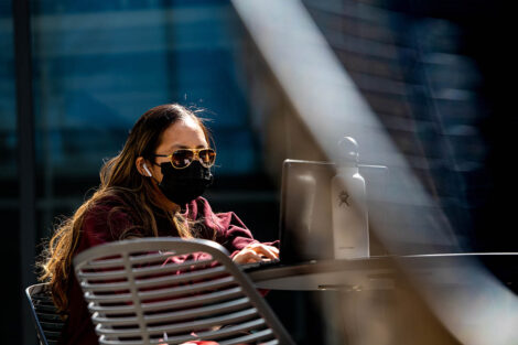 A masked student sits at a table outside, typing on their laptop; a reusable water bottle is also on the table.