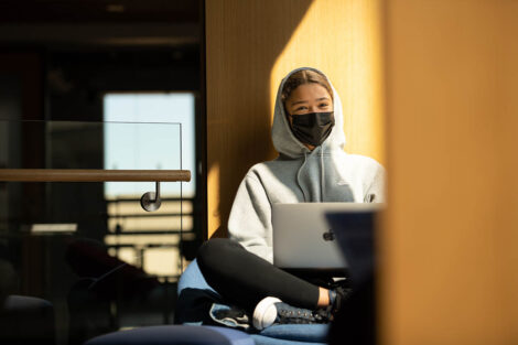 A masked student, with their sweatshirt hood up, sits with their laptop open inside of Rockwell Integrated Sciences Center
