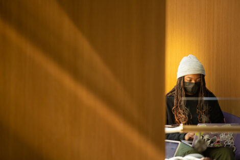A masked student in a hat, sits in front of their laptop in Rockwell Integrated Sciences Center