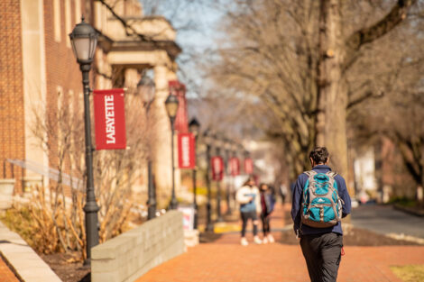Students walk away from the camera on a brick sidewalk, lined with lamp posts and Lafayette College flags, in front of Markle Hall.
