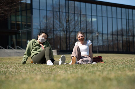 Two masked students sit in grass in front of Skillman Library.