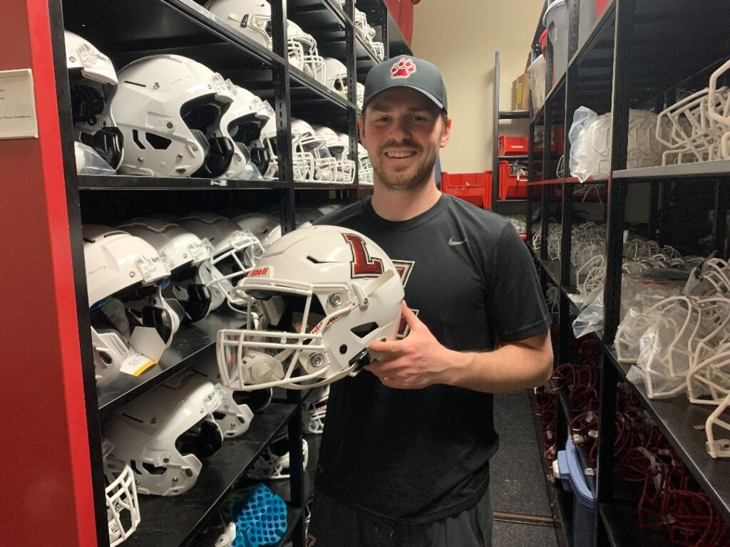 Seth Holiday, director of equipment services, displays helmet with face shield