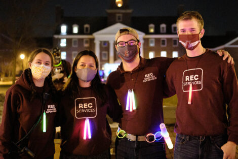 student workers with Rec Services wear masks and glowsticks around their necks