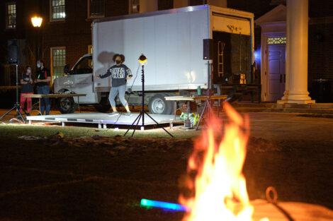 a fire pit illuminates a lead dancer