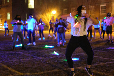 students dance at night wearing masks and holding glow sticks