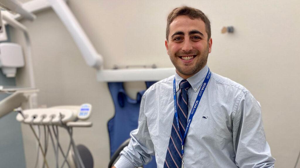 Alec Eidelman stands in front of dental equipment.