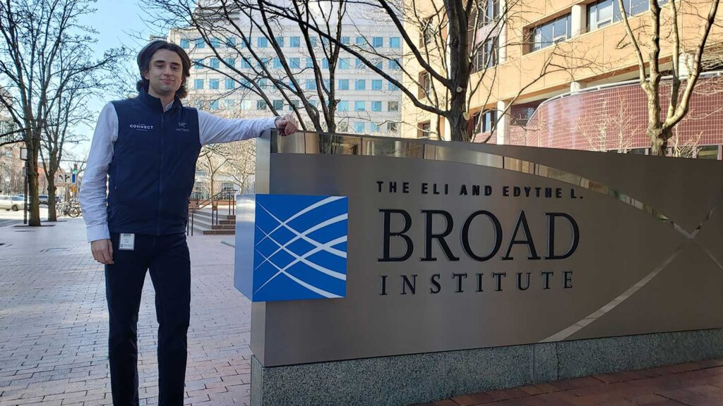 Andrew Hudak standing outside next to Broad Institute sign