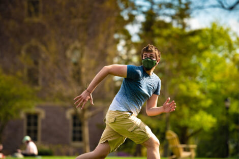 A masked student runs to retrieve a frisbee.