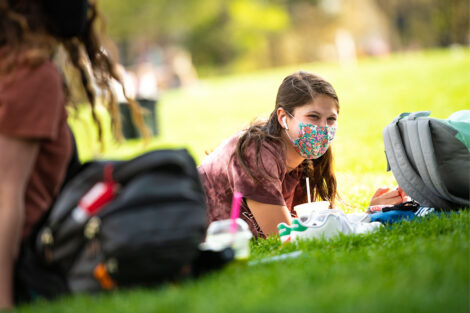 A masked student studies on the Quad.