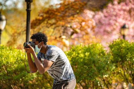 A masked student uses camera to take photos of campus.