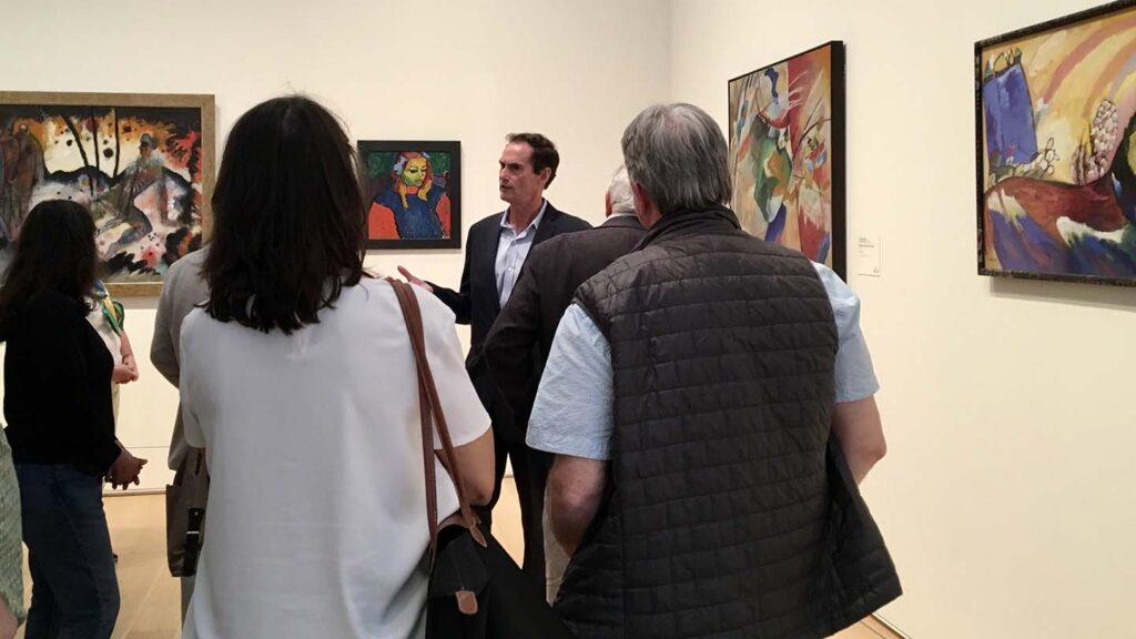 Bob Mattison speaks to alumni in a gallery with several paintings on the wall behind him