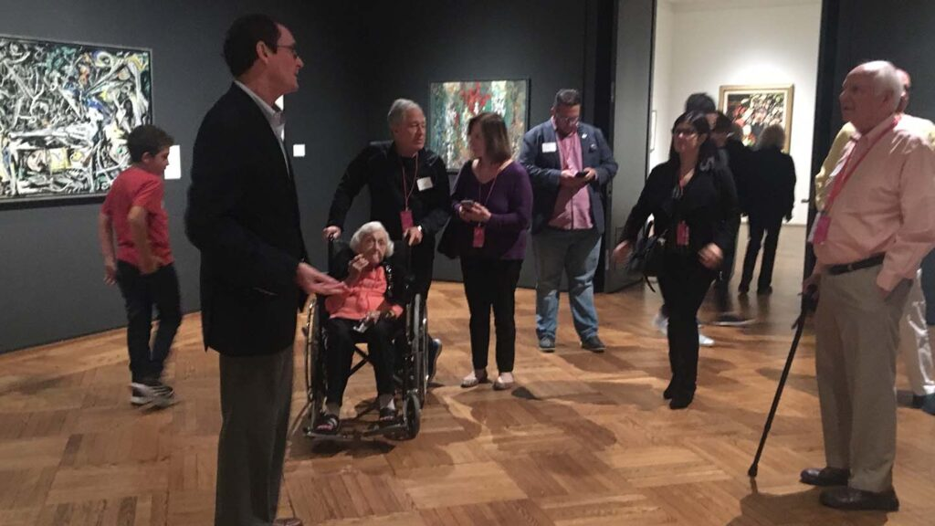 People stand around Bob Mattison in a gallery and ask him questions
