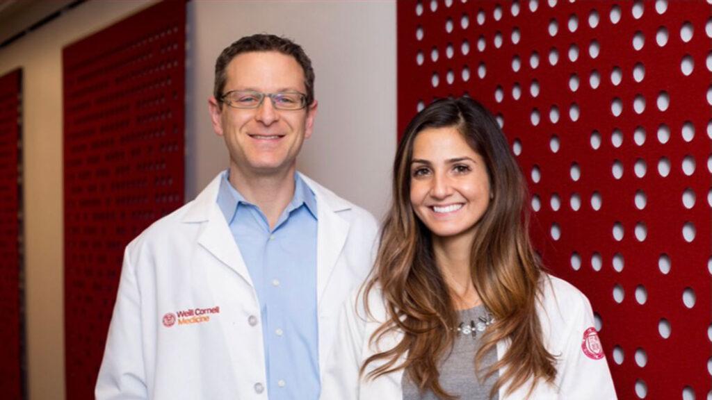 Kellyann Niotis, wearing white lab coat, stands next to her mentor, Dr. Richard Isaacson.