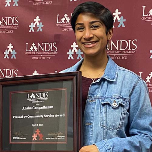 Alisha Gangadharan holds a framed certificate in front of the Landis Center logo