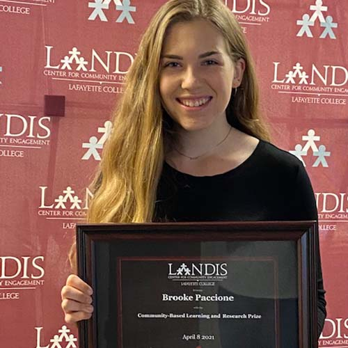 Brooke Paccione holds a framed certificate in front of the Landis Center logo
