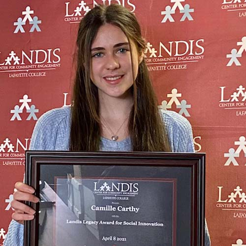 Camille Carthy holds a framed certificate in front of the Landis Center logo