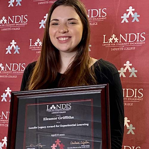 Eleanor Griffiths holds a framed certificate in front of the Landis Center logo