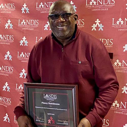 Fluney Hutchinson holds a framed certificate in front of the Landis Center logo