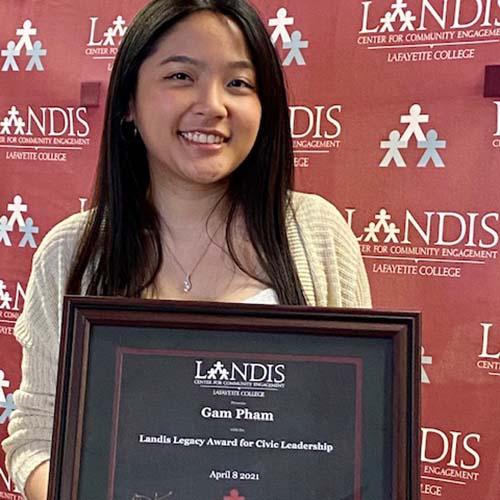 Gam Pham holds a framed certificate in front of the Landis Center logo
