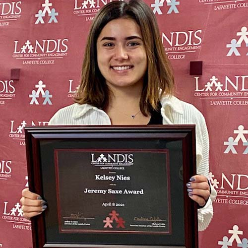 Kelsey Nies holds a framed certificate in front of the Landis Center logo