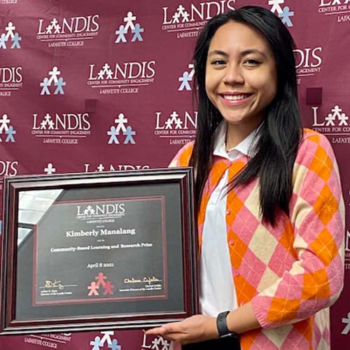 Kim Manalang holds a framed certificate in front of the Landis Center logo