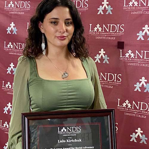 Lulu Kirtchuk holds a framed certificate in front of the Landis Center logo