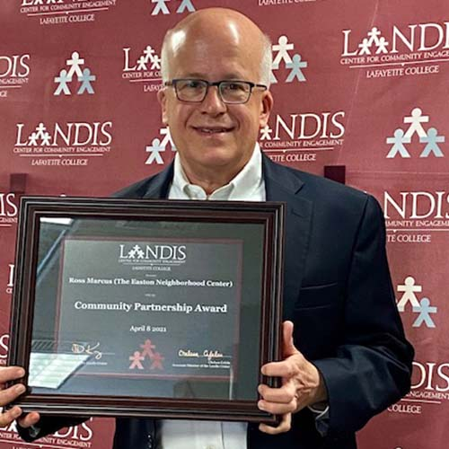 Ross Marcus holds a framed certificate in front of the Landis Center logo