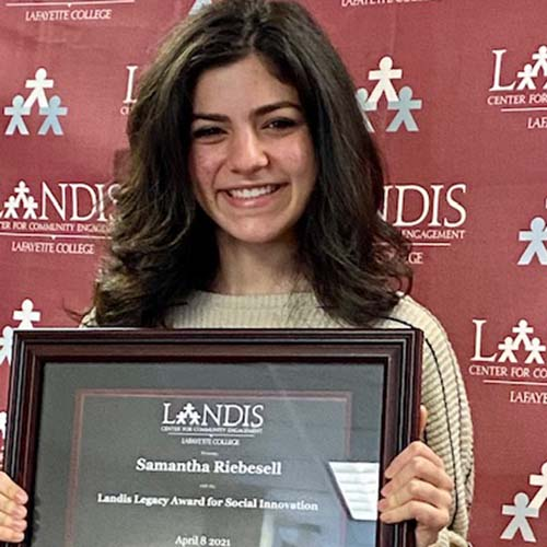 Samantha Riebesell holds a framed certificate in front of the Landis Center logo