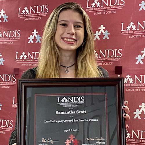 Sam Scott holds a framed certificate in front of the Landis Center logo