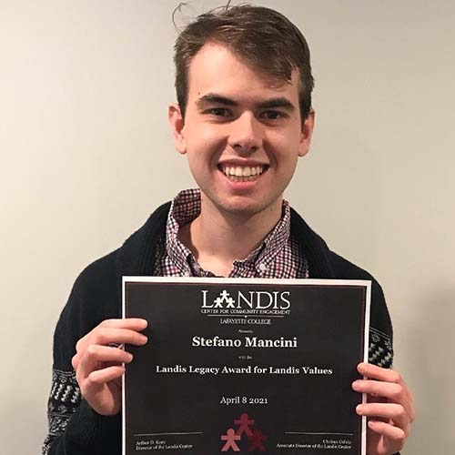 Stefano Mancini holds a framed certificate in front of the Landis Center logo