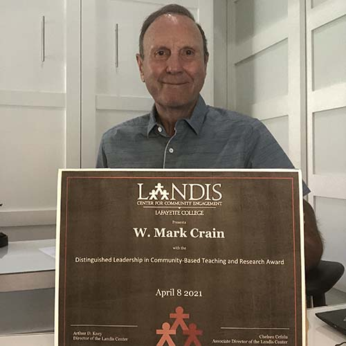 W. Mark Crain holds a framed certificate in front of the Landis Center logo
