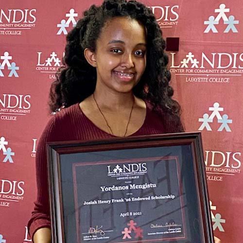 Yordanos Mengistu holds a framed certificate in front of the Landis Center logo