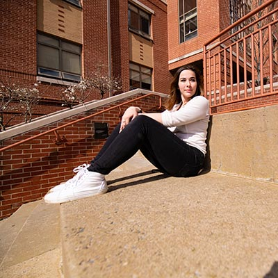 Student sits on oversized step with her elbows on her knees near Simons dining location