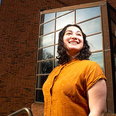 Student in orange blouse looks upward with the brick and glass of Williams Center for the Arts behind her