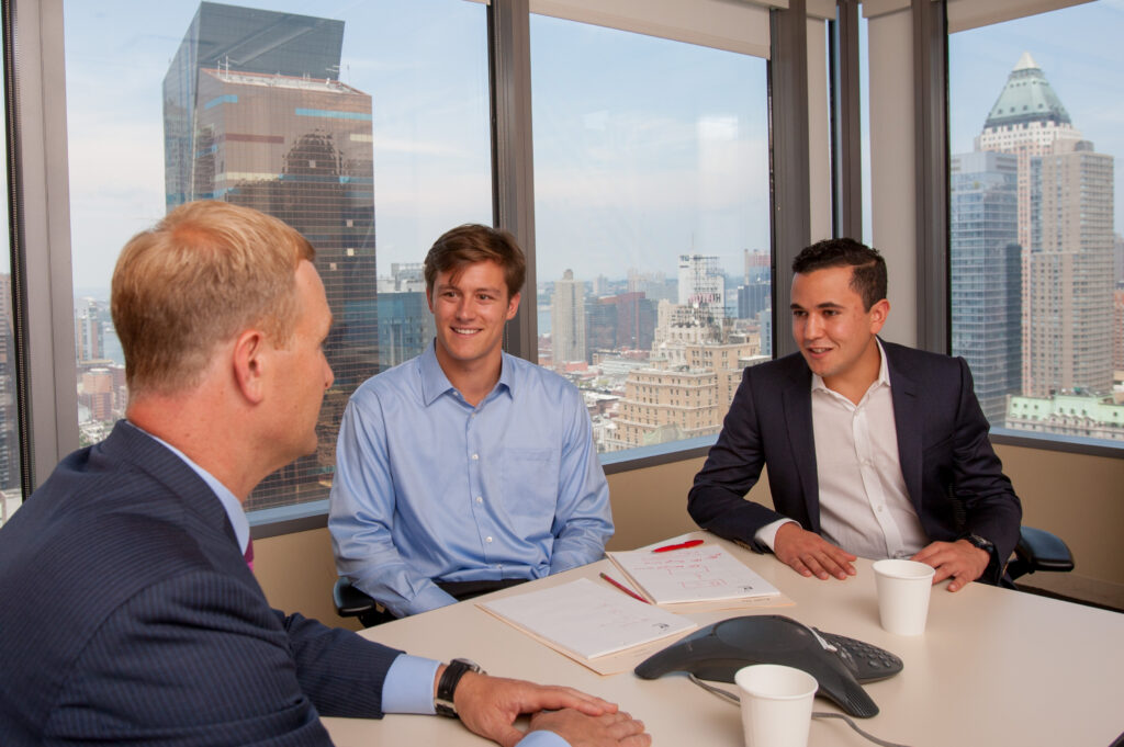 Image of Othman Guennoun '17 when he was a student as he and another student intern at EY. They sit around a table with cups of coffee and the NYC skyline behind them.