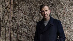 Robert Macfarlane stands outside, tree behind him