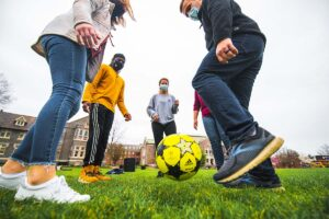 Five masked students stand in a circle, kicking a ball in front of Hogg Hall and Farinon College Center