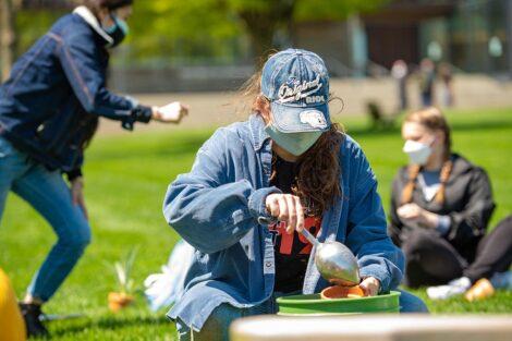 A student wearing a mask shovels soil into a pot.