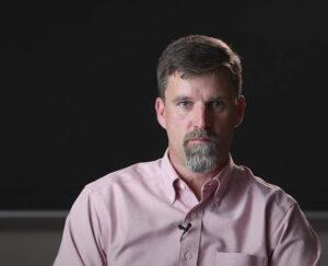 Trent Gaugler sits in classroom with blackboard behind him