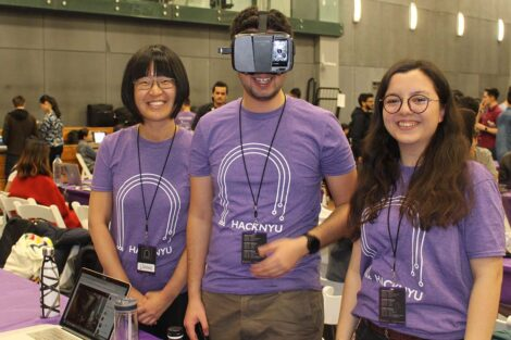 Rabia is in a purple NYU Hackathon tee shirt along side her team: a woman smiling and a man in a virtual headset