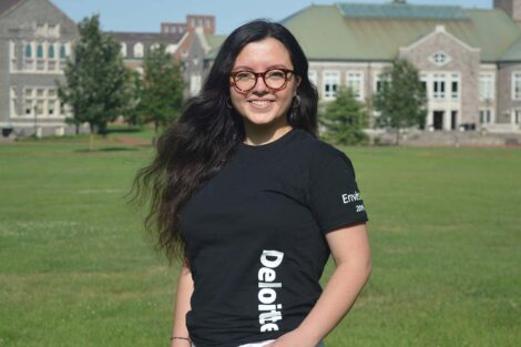 Rabia stands on the quad in a black tee shirt with the name Deloitte on the side in white letters