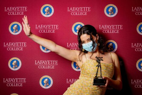 Alexandra Kirtchuk '21 holding Aaron O. Hoff Award statue and standing in front of Lafayette College backdrop
