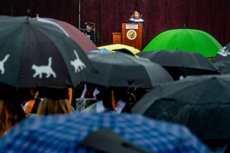 Alison Byerly addresses seniors, crowd filled with umbrellas