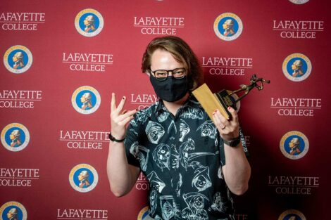 Andrew Bachman '21 holding Aaron O. Hoff Award statue and standing in front of Lafayette College backdrop