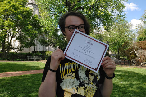 Andrew Bachman holds certificate