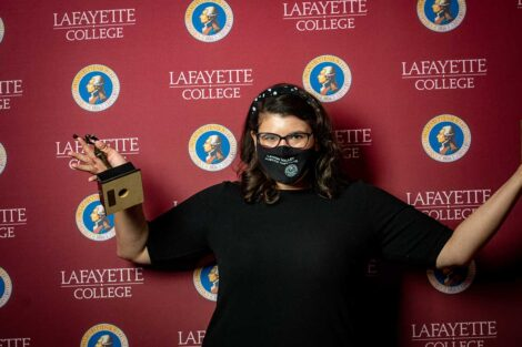 Angela Bell holding Aaron O. Hoff Award and standing in front of Lafayette College backdrop